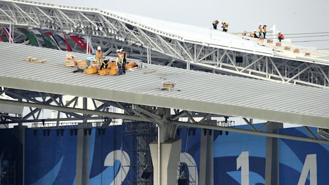 Workers install fireworks on the roof of the 17th Asian Games main stadium ahead of the opening ceremony in Incheon, west of Seoul, South Korea, Monday, Sept. 15, 2014. The games will be held in the South Korea's western city from Sept. 19 to Oct. 4. (AP Photo/Rob Griffith)