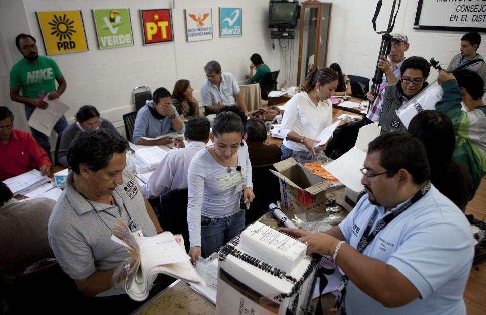 Election officials and party representatives begin a computation of ballot boxes at an electoral institute district council in Mexico City, Wednesday, July 4, 2012. The computation is done to determine which ballot boxes used in last Sunday's general elections will be recounted in front of party representatives. (AP Photo/Eduardo Verdugo)