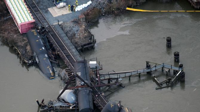 Several cars lay in the water after a freight train derailed in Paulsboro, N.J., Friday, Nov. 30, 2012. People in three southern New Jersey towns were told Friday to stay inside after the freight train derailed and several tanker cars carrying hazardous materials toppled from a bridge and into a creek. (AP Photo/Cliff Owen)