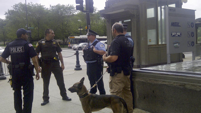 Chicago police officers with a police dog stand outside the Metra commuter line's Millennium Station near Chicago's Grant Park Monday morning, May 21, 2012. Commuter traffic appears to be down in Chicago as the NATO summit enters its second and final day. Many companies heeded official advice and are letting their workers stay home for the day. (AP Photo/Ryan J. Foley)