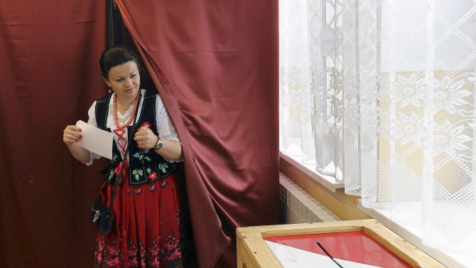 A woman wears a traditional outfit as she prepares to cast her ballot during the second round of presidential elections at a polling station in Zakopane