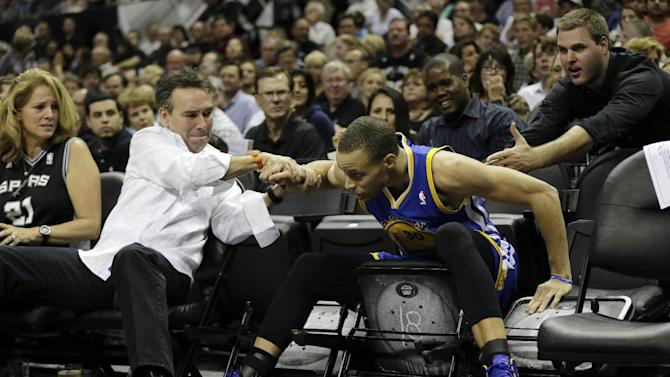 After making a three-point basket against the San Antonio Spurs, Golden State Warriors point guard Stephen Curry (30) his helped when he fell into the seats during the second half of Game 1 of a Western Conference semifinal NBA basketball playoff series, Monday, May 6, 2013, in San Antonio. (AP Photo/Eric Gay)