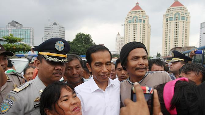 In this photo taken on Jan. 3, 2013, Jakarta Gov. Joko Widodo, center, poses with his supporters for photographers during his inspection of bus transportation in Jakarta, Indonesia. Widodo's trip through his inundated city of 14 million reflected his hands-on approach to leadership, a style that helped him win election in September against an incumbent who was backed by the establishment political parties. His traffic plans include more buses to ply the city's dedicated lanes, some of which have already arrived, more roads and a scheme that would restrict the amount of cars that travel into the city center each day based on whether their license plate ends in odd or even number. (AP Photo/Achmad Ibrahim)