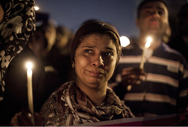 In this Saturday Feb. 2, 2013 photo, demonstrators hold candles in memory of protester Mohammed Qorany, at the spot where he died in clashes, near the presidential palace in Cairo, Egypt. Protesters a
