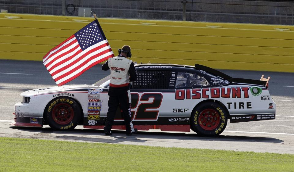 A crew member hands Brad Keselowski a United States flag after he won the NASCAR Nationwide Series History 300 auto race in Concord, N.C., Saturday, May 26, 2012. (AP Photo/Chuck Burton)