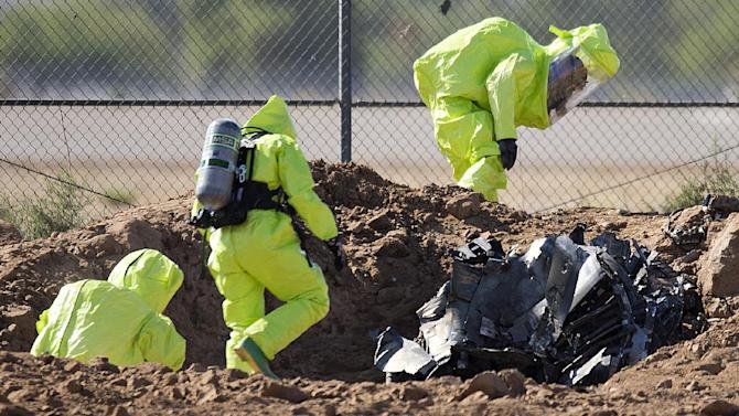 Investigators look at the debris from an F 16 that crashed at Luke Air Force Base Wednesday, June 26, 2013. An F-16 fighter jet crashed but authorities said both pilots ejected safely. (AP Photo/The Arizona Republic, Tom Tingle)