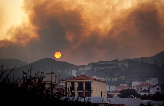 Smoke billows across houses as a wildfire burns near Chipude Village, La Gomera, Spain, Sunday, Aug. 12, 2012.  Wildfires spurred by high temperatures raged across Spain's Canary Islands of La Gomera