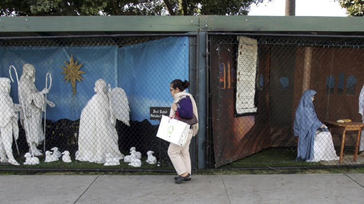 "FILE - In this Dec. 13, 2011 file photo, a woman walks past a two of the traditional displays showing the Nativity scene along Ocean Avenue at Palisades Park in Santa Monica, Calif. Avowed atheist Damon Vix last year won two-thirds of the booths in the annual, city-sponsored lottery to divvy up spaces in the live-sized Nativity display.  But he only put up one thing: A sign that read ""Religions are all alike - founded on fables and mythologies."" Vix left the rest of his allotted spaces empty, and in so doing, upended a Christmas tradition that began in Santa Monica nearly 60 years ago. (AP Photo/Ringo H.W. Chiu, file)"