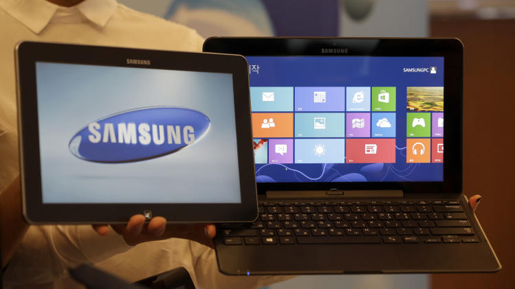Samsung Electronics Co's ATIV smart PC and tablet, powered by a new version of Microsoft's Windows operating system, are shown at a media briefing in Seoul, South Korea, Wednesday, Oct. 24, 2012. Samsung said Wednesday it expects 10 percent growth in PC sales by volume this year as it bets on new PCs that are hybrids of laptops and tablets to lift sluggish PC demand. (AP Photo/Lee Jin-man)