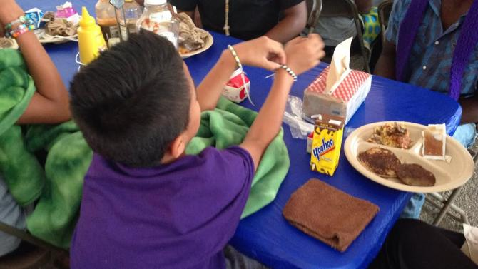 A migrant child sits during a meal at the Naval Base Ventura County Temporary Shelter in Port Hueneme, California