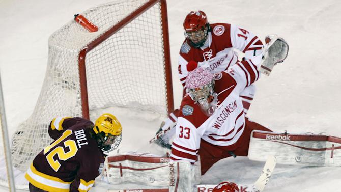 Wisconsin forward Sean Little (18) keeps Minnesota defenseman Justin Holl (12) from taking a shot on-goal as goalie Joel Rumpel (33) and Jefferson Dahl (14) watch during the third period of college hockey game at Chicago's Soldier Field, Sunday, Feb. 17, 2013. Wisconsin upset Minnesota 3-2. (AP Photo/Charles Rex Arbogast)