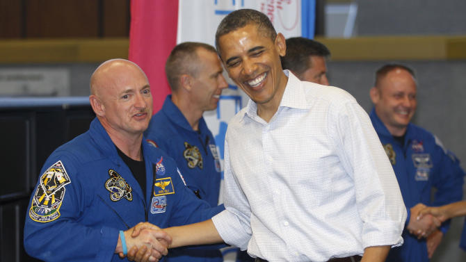President Barack Obama meets with Space Shuttle Endeavor commander Mark Kelly, husband of wounded Rep. Gabrielle Giffords, D-Ariz., and shuttle astronauts, after their launch was scrubbed, Friday, April 29, 2011, at Kennedy Space Center in Cape Canaveral, Fla. (AP Photo/Charles Dharapak)