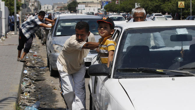 In this Sunday, May 29, 2011 file photo volunteers push queued cars closer to the pumps at the women-only Gurji fuel station in Tripoli, Libya. (AP Photo/Ivan Sekretarev, File)