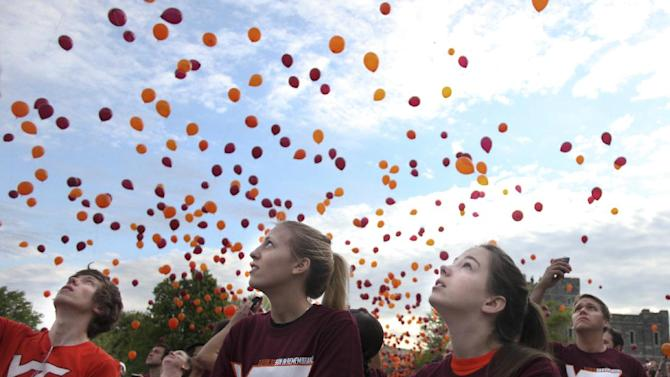 FILE - In this Saturday, April 14, 2012 file photo, Paige Eckerd, right, and Kristy McCain, center, look skyward at released balloons at the start of a Run in Remembrance on the Virginia Tech campus in Blacksburg, Va. The 3.2-mile Run in Remembrance for the victims of the April 16, 2007, Virginia Tech shootings had about 6,500 participants registered in advance for the event in honor of the 32 killed in the deadliest mass shooting in modern U.S. history. Each anniversary since the April 2007, massacre on the Virginia Tech campus, classes have been suspended for the day in memory of the 32 students and faculty killed in the rampage by a lone gunman who then killed himself. On Monday, April 16, 2012, the fifth anniversary of the deadliest mass shooting in modern U.S. history, the 28,000 students on campus will head to class to honor the 32. (AP Photo/The Roanoke Times, Matt Gentry, File)