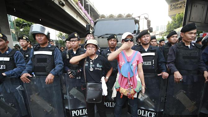 """Two protesters, center, gesture in front of line of Thai riot police officers during an anti-coup demonstration at the Victory Monument in Bangkok, Thailand Monday, May 26, 2014. Bolstered by a royal endorsement Monday to run the country after last week's coup, Thailand's junta leader warned citizens not to cause trouble, not to criticize, not to protest, or else face a return to the """"old days"""" of street violence. (AP Photo/Wason Wanichakorn)"""