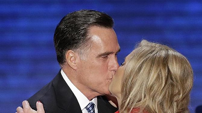 FILE - In this Aug. 28, 2012, file photo, Ann Romney is kissed by her husband Republican presidential nominee Mitt Romney during the Republican National Convention in Tampa, Fla. Politicians have always tried to connect with voters. Kissing babies has long been a campaign requirement. People like to see passion in their candidates. Romney, for his part, delivered a more standard bye-honey-see-you-tonight kiss on the lips on his convention stage this year. But he does seem more at ease now than back in the primaries, when he rather awkwardly pretended that a waitress at a New Hampshire diner had goosed him. (AP Photo/J. Scott Applwhite, File)