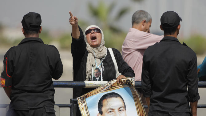 An Egyptian pro-Mubarak supporter shouts slogans as she holds a poster of former Egyptian President Hosni Mubarak, outside a court in Cairo Egypt, Saturday, May 11, 2013. Egyptian prosecutors say they are presenting new evidence in the retrial of former President Hosni Mubarak, for failing to stop the killing of 900 protestors in the 2011 unrest that ousted him.  (AP Photo/ Amr Nabil)