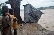 "Haitians view flooding from heavy rains as a result of Hurricane Sandy in Port-au-Prince, Haiti. Hurricane Sandy pounded the Bahamas on Thursday, and headed toward the US East Coast on a path which forecasters warned could lead to the creation of a powerful hybrid ""Frankenstorm"" next week"