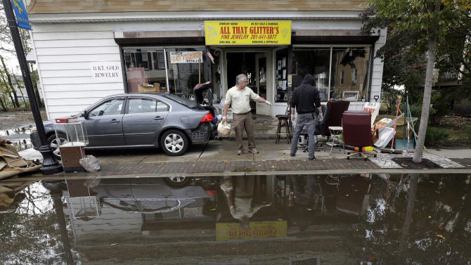 Charles Vartanian, left, and his son Chris clear out flood-damage items from his store in the wake of superstorm Sandy on Thursday, Nov. 1, 2012, in Little Ferry, N.J. Surprise coastal surge floods caused by the storm battered Little Ferry, Moonachie and some other towns along the Hackensack River in Bergen County _ all areas unaccustomed to flooding. (AP Photo/Mike Groll)