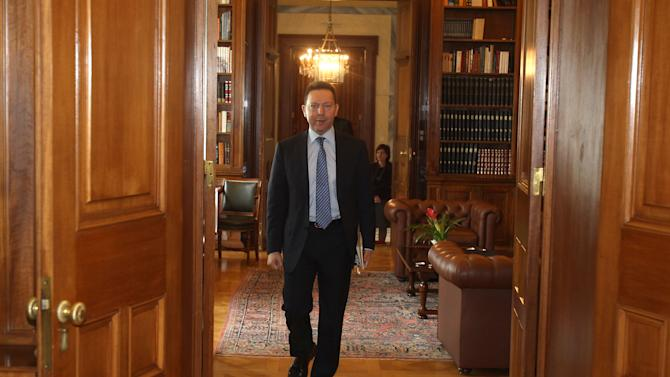Greece's Finance Minister Yannis Stournaras arrives for a meeting with President Karolos Papoulias, unseen, at the Presidential Palace in Athens, Tuesday, March 26, 2013.  Greece's Piraeus Bank reached an agreement Tuesday to buy the Greek operations of three Cypriot banks for euro524 million ($677.79 million), but markets opened after a long weekend hammered by continued uncertainty over the island's finances. (AP Photo/Thanassis Stavrakis)