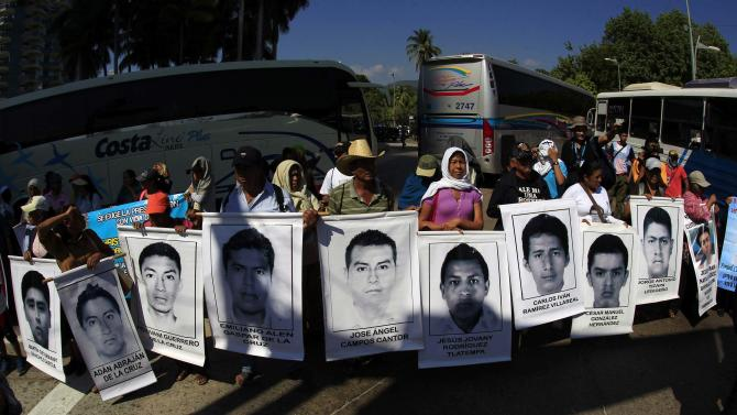 Relatives of the 43 missing students from Ayotzinapa Teacher Training College hold portraits of the students during a demonstration in Acapulco, Guerrero