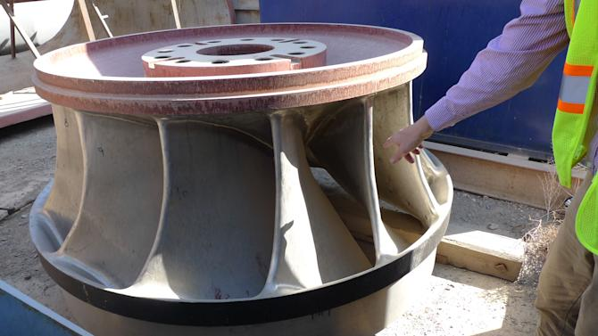 In this Thursday, Nov. 15, 2012 photo, a U.S. contractor shows reporters a key part of a turbine waiting to be installed at the Kajaki dam in Helmand province, south of Kabul, Afghanistan. (AP Photo/Heidi Vogt)