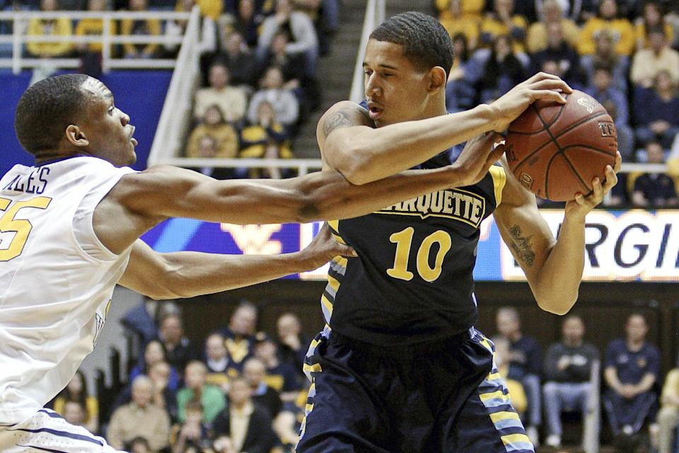 West Virginia's Keaton Miles, left, pressures Marquette's Juan Anderson (10) in the first half of an NCAA college basketball game, Friday, Feb. 24, 2012, in Morgantown, W.Va. (AP Photo/David Smith)