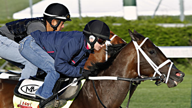 Jockey Rosie Napravnik, right, works Kentucky Derby hopeful Vicar's in Trouble with a stablemate at Churchill Downs in Louisville, Ky., Saturday, April 26, 2014. (AP Photo/Garry Jones)