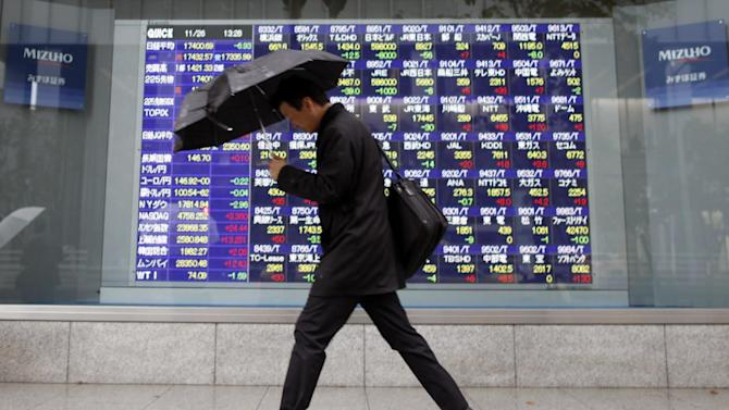 A businessman walks past an electronic stock indicator of a securities firm in Tokyo Wednesday, Nov. 26, 2014. Asian stock markets mostly posted modest gains Wednesday as stronger U.S. growth was tempered by a less rosy outlook for China. Japan's Nikkei 225 dropped 0.1 percent to 17,399.73 while China's Shanghai Composite rose 0.5 percent to 2,580.85. (AP Photo/Shuji Kajiyama)