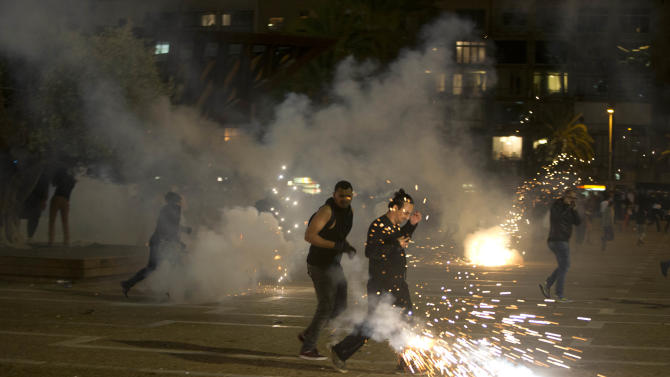 """Israel's mainly Jewish Ethiopians clash with Israeli riot police during a protest against racism and police brutality in Tel Aviv, Israel, Sunday, May 3, 2015, as several thousand people from Israel's Jewish Ethiopian minority protest, shutting down a major highway and clashing with police on horseback long into the night. The protest was mostly peaceful during the day, but by nightfall became violent with at least 20 officers were hurt and """"multiple protesters"""" arrested, Police Spokesman Micky Rosenfeld said.(AP Photo/Oded Balilty)"""