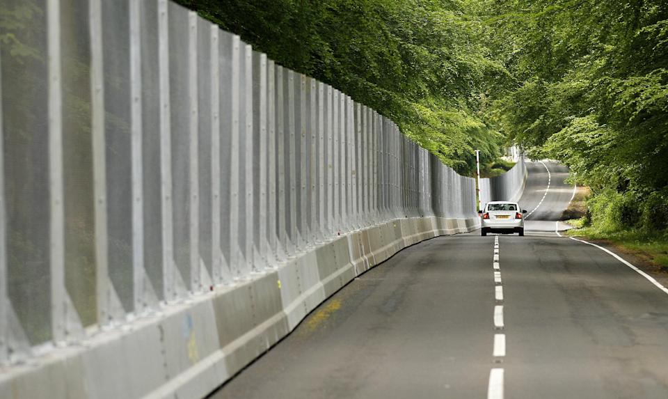 A car makes its way along a security fence erected around the G8 venue, the Lough Erne Golf Resort, in Enniskillen, Northern Ireland, Thursday, June 6, 2013.  (AP Photo/Peter Morrison)