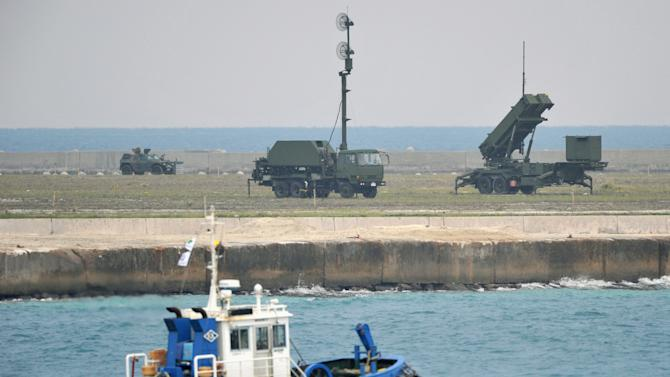 A fishing boat sails by a ground-based Patriot Advanced Capability-3 interceptor, right, and other vehicles deployed to prepare for North Korea's planned launch of a long-range rocket at a port in Ishigaki on Ishigaki Island, Okinawa Prefecture, southwestern Japan, Monday morning, Dec. 10, 2012. North Korea held off launching a long-range rocket Monday, the first day of a 13-day window during a frigid, snowy stretch of winter weather, a day after announcing it may delay the controversial liftoff. (AP Photo/Kyodo News) JAPAN OUT, MANDATORY CREDIT, NO LICENSING IN CHINA, FRANCE, HONG KONG, JAPAN AND SOUTH KOREA