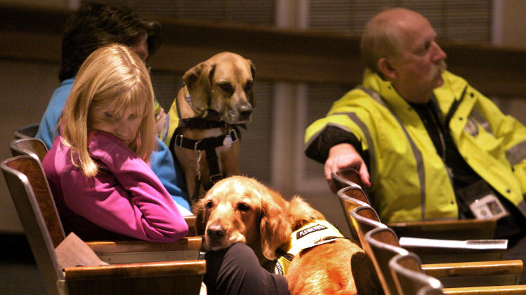 Glen Hoffman, left, of Extra Mile Ministries with K9 crisis comfort dog Beau, listen during a community meeting at Newtown High school on the future of Sandy Hook Elementary School in Newtown, Conn., Sunday, Jan. 13, 2013. Talk about Sandy Hook Elementary School is turning from last month's massacre to the future, with differing opinions on whether students and staff should ever return to the building where a gunman killed 20 students and six educators. (AP Photo/Michelle McLoughlin, Pool)