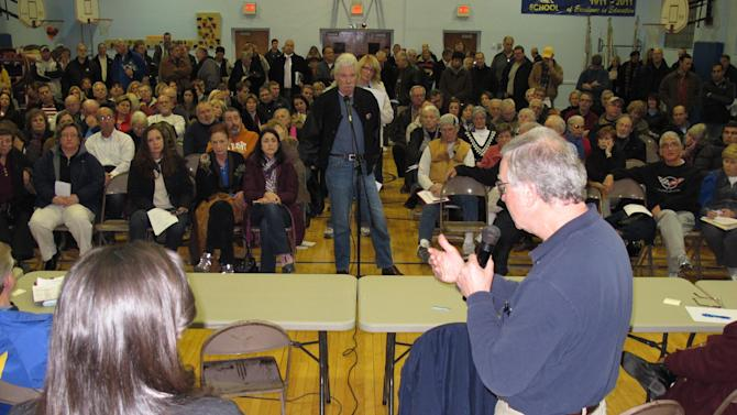 A FEMA representative, right, speaks to an audience of Sea Bright N.J. residents at a town meeting held in nearby Oceanport N.J. on Jan. 3, 2013 to provide information about the rebuilding process following Superstorm Sandy. Sea Bright's entire business district was wiped out (four shops have since re-opened) and 75 percent of residents are still homeless. Yet Sea Bright is determined to rebuild as a debate rages on whether to restore shore communities to their pre-storm condition, or buy out properties in flood-prone areas and depopulate them. (AP Photo/Wayne Parry)