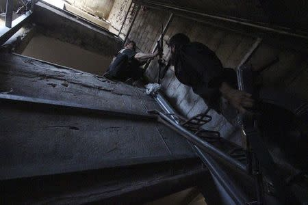Rebel fighter hands weapon to fellow fighter as they move inside building on frontline in Damascus suburb of Harasta