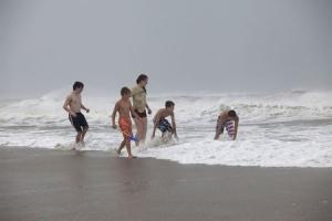 Children play in the surf of Hurricane Arthur, at the west end of Ocean Isle Beach, North Carolina