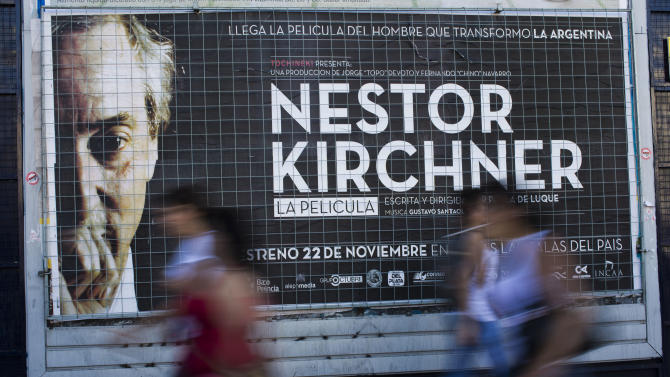 """People walk by a banner promoting the documentary film """"Nestor Kirchner"""" in Buenos Aires, Argentina, Wednesday, Nov. 21, 2012. The film hits the theaters on Thursday, the latest example of an ongoing effort to exalt the late president's memory, seeking to match the level of Juan Domingo Peron.  Streets, hospitals, tunnels and even a soccer tournament is named after Nestor Kirchner, who served as president from 2003 to 2007 and died at the age of 60 on Oct. 27, 2010. (AP Photo/Natacha Pisarenko)"""