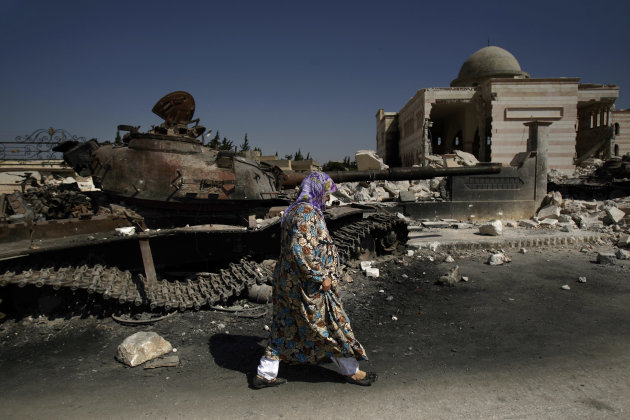 A Syrian woman walks past a government tank which was destroyed by the rebels in Azaz, on the outskirts of Aleppo, Syria, Tuesday, Aug. 28, 2012. (AP Photo/Muhammed Muheisen)
