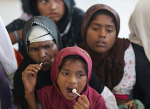 Ethnic rohingya women eat candy at a temporary shelter…