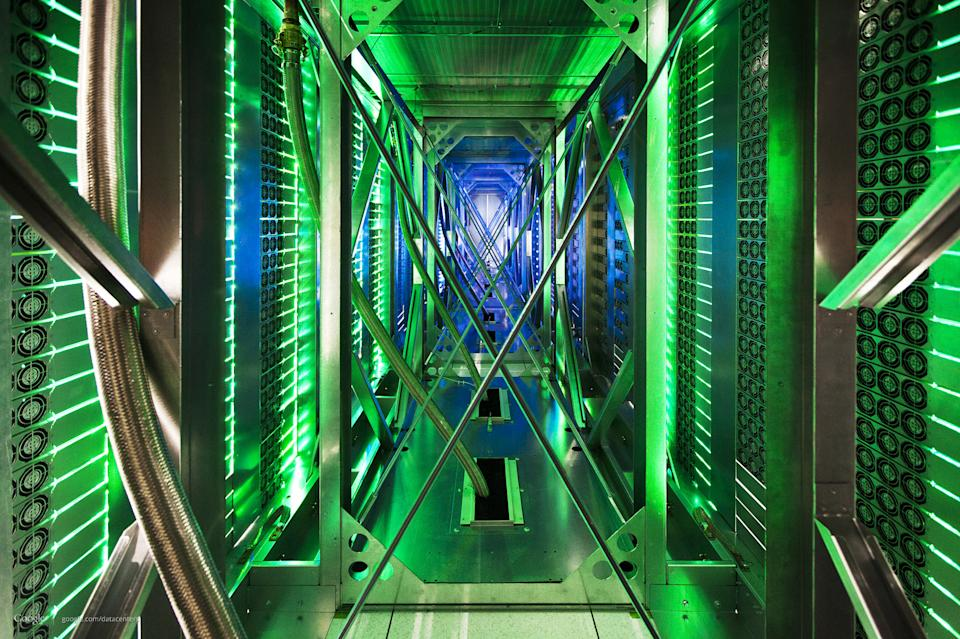 In this undated photo made available by Google, hundreds of fans funnel hot air from the computer servers into a cooling unit to be recirculated at a Google data center in Mayes County. Okla. The green lights are the server status LEDs reflecting from the front of the servers. (AP Photo/Google, Connie Zhou)