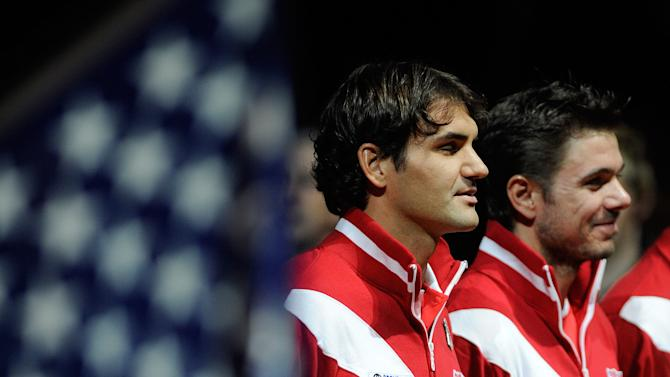 Swiss Roger Federer (L), world number three, and his teammate Stanislas Wawrinka stand during the Opening ceremony of the Davis Cup World Group first round game opposing Switzerland to USA on February 10, 2012 in Fribourg.     AFP PHOTO/ SEBASTIEN FEVAL (Photo credit should read SEBASTIEN FEVAL/AFP/Getty Images)