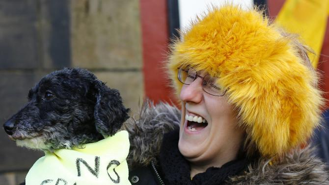 A woman holds a dog during an anti-fracking protest in Preston