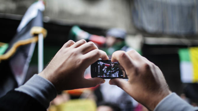 A Syrian man uses his mobile phone to capture a child using a megaphone to lead others in chanting Free Syrian Army slogans during a demonstration in the neighborhood of Bustan Al-Qasr, Aleppo, Syria, Friday, Jan. 4, 2013. The U.N. said Wednesday that more than 60,000 people have been killed since Syria's crisis began in March 2011 — a figure much higher than previous opposition estimates. (AP Photo/Andoni Lubaki)
