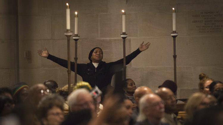 A woman raises her arms during a memorial service for the late Nelson Mandela at the Riverside Church in New York