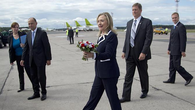 U.S. Secretary of State Hillary Rodham Clinton walks with a bouquet of flowers she received after arriving in Riga, Latvia, Thursday, June 28, 2012. According to the State Department, Clinton has set a new frequent-flier record, touching down in her 100th country as America's top diplomat. She has made 70 trips, completed 337 days on the road, and spent the equivalent of over 73 days on the plane, equaling over 1,750 hours. (AP Photo/Haraz N. Ghanbari, Pool)