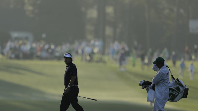 Phil Mickelson walks across the first fairway with his caddie Jim MacKay during a practice round for the Masters golf tournament Tuesday, April 9, 2013, in Augusta, Ga. (AP Photo/Charlie Riedel)