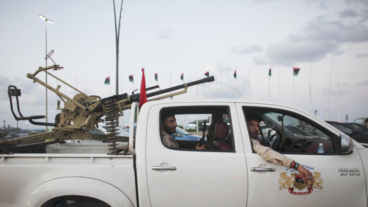 Revolutionary fighters sit in a pickup truck in Tripoli, Libya, Thursday, Sept. 29, 2011. More than a month since revolutionary forces seized the Libyan capital, the heavy thud of anti-aircraft guns and the crackle of automatic weapon fire still echoes across the city, and bands of young fighters in pickup trucks bristling with heavy weapons cruise the streets. (AP Photo/Alexandre Meneghini)