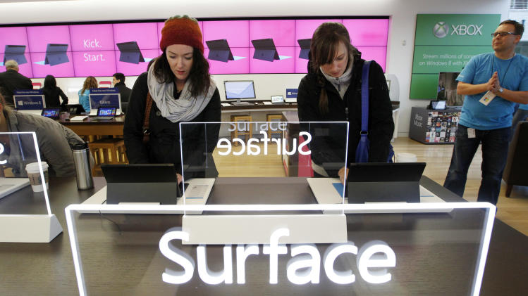 Caitlin Mullock, left, and Jessica Toman look over new Microsoft Surface tablet computers Friday, Oct. 26, 2012, at a Microsoft store in Seattle. Friday was the first day of sales for the new Windows 8 operating system and the company's new tablet computer, the Surface. (AP Photo/Elaine Thompson)