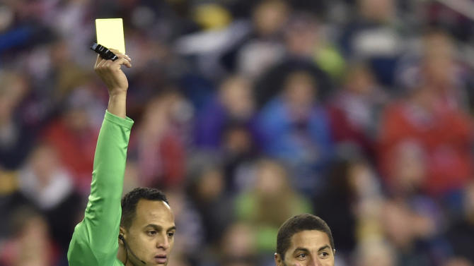 Real Salt Lake forward Alvaro Saborio, right, reacts as he receives a yellow card from referee Ismail Elfath in the second half of  his team's MLS soccer match against the New England Revolution in Foxborough, Mass.,  Saturday, April 25, 2015. (AP Photo/Gretchen Ertl)