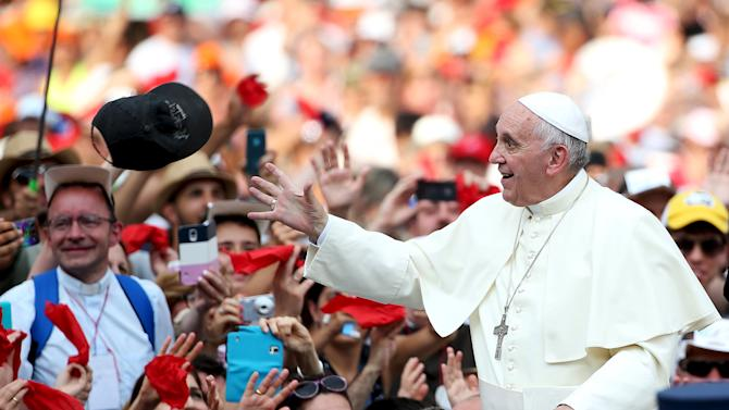 Pope Francis tries to take a cap as he arrives to lead a special audience for members of the Renewal in the Holy Spirit movement  in Saint Peter's square at the Vatican